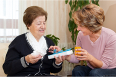 A caregiver giving an elderly her medications