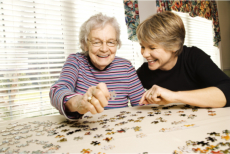 A caregiver and an elderly playing a puzzle game