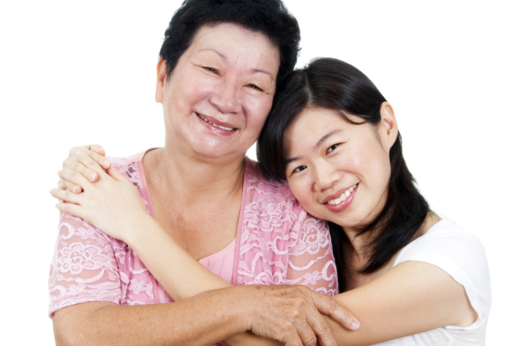 Asian caregiver hugging an elderly